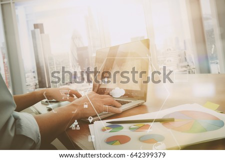 businessman working with mobile phone and digital tablet and laptop computer on wooden desk in modern office with VR icon and graph diagram