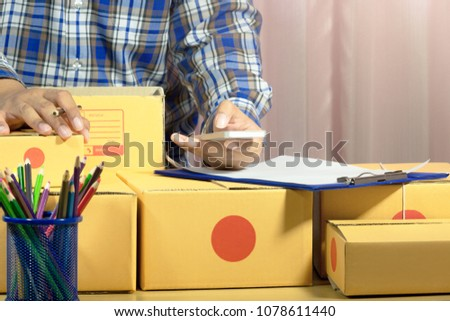 Businessman working with mobile phone and packing brown parcels box at home office. hands seller prepare product ready for deliver to customer. Online selling, e-commerce Start up shipping concept.