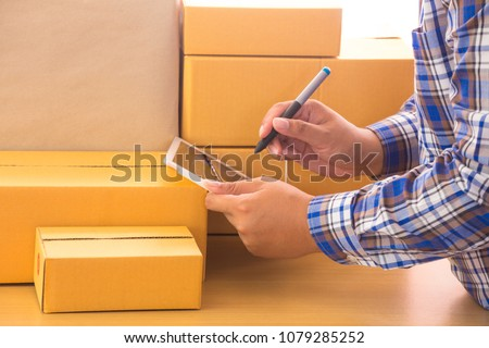 Businessman working with mobile phone and packing brown parcels box at home office. hands seller prepare product ready for deliver to customer. Online selling, e-commerce Start up shipping concept