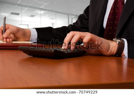 Businessman working working with a calculator in the office, while writing something