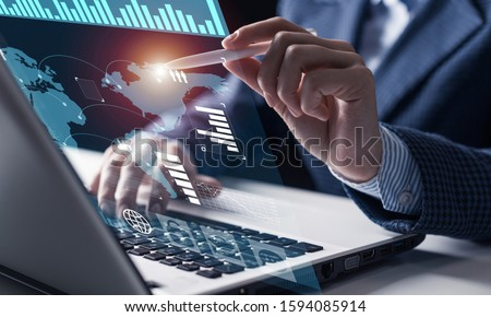 Businessman works with financial data. Futuristic 3d interface above laptop computer. Interactive financial diagrams and digital data visualization concept. Global e-business network communication
