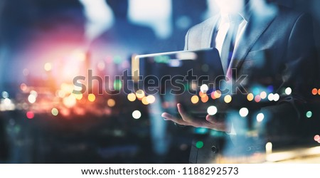 Businessman works with his laptop during the night. double exposure #1188292573