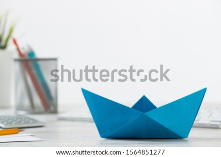 Businessman workspace at office desk with blue paper ship. Flat lay wooden table on white background. Close up blue origami boat. Creative and innovative solution for business. #1564851277