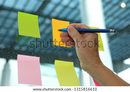 Businessman write on adhesive notes on glass wall at workplace. Sticky note paper reminder schedule for discussing creative idea & business brainstorming #1315816610