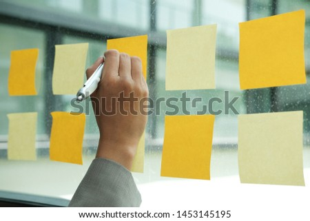 Businessman write on adhesive notes on glass wall at workplace. Sticky note paper reminder schedule for discussing creative idea & business brainstorming