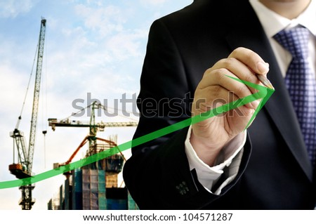 Businessman write on virtual board with construction site background