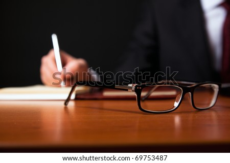 Businessman writing documents in low light. Focus on a pair of glasses.