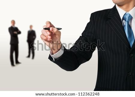 Businessman writing, drawing on the screen. Teamwork - stock photo