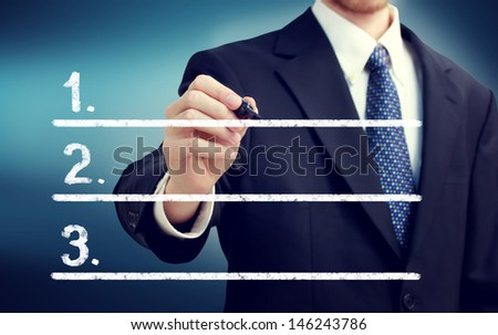 Businessman writing lists with navy blue background