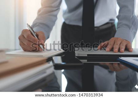 Businessman writing notes on paper notebook while working on laptop computer in modern office. Project manager planning his work on notepad with mobile phone on office desk, close up