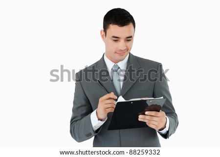 Businessman writing on clipboard against a white background