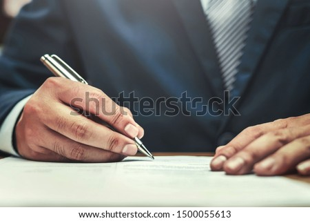 businessman writing on paper report in office concept