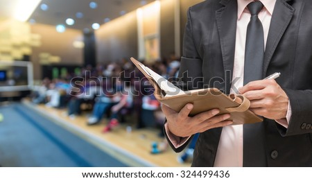 Businessman writing the note book on the Abstract blurred photo of conference hall or seminar room with attendee background