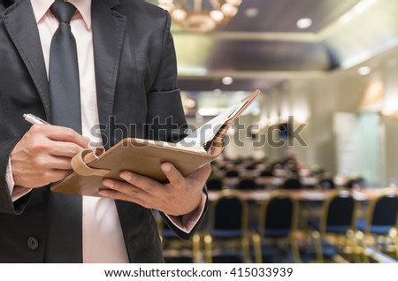 Businessman writing the note book on the Abstract blurred photo of conference hall or seminar room background