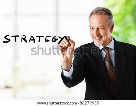 Businessman writing the word strategy on the screen