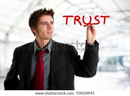 Businessman writing the world Trust on the screen - stock photo