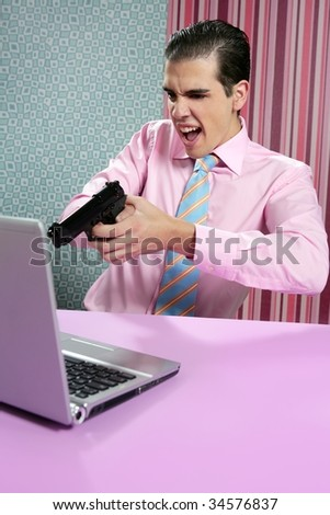businessman young shooting handgun with computer pink bacground
