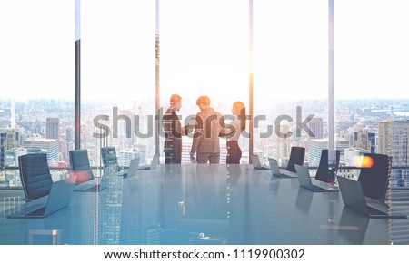 Businessmen and a businesswoman talking in a modern panoramic office boardroom with a gray table. 3d rendering mock up toned image double exposure