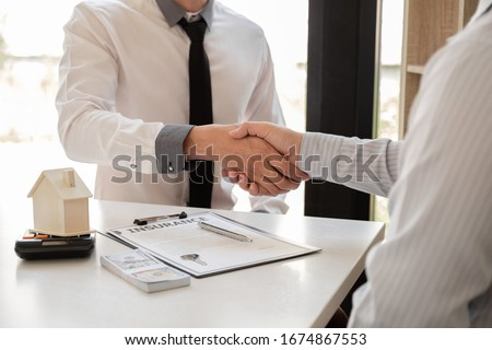 Businessmen and brokers real estate agents catch hand after completing negotiations to buy houses insurance and sign contracts. Home insurance concept. Stock foto ©