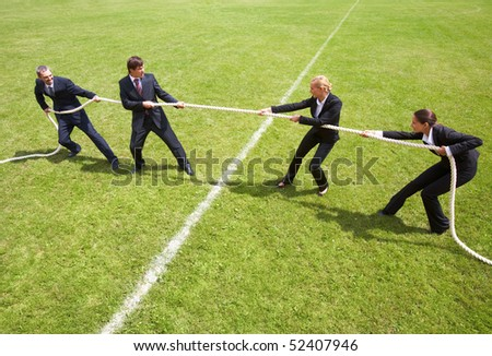 Businessmen and businesswomen playing tug of war