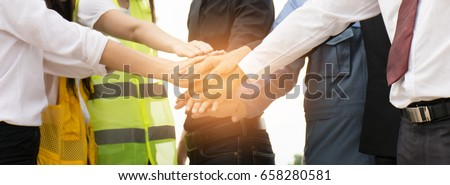 Businessmen and engineers join hands to build successful projects. Teamwork concept. #658280581