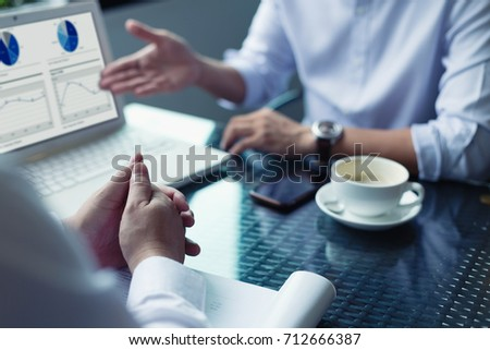 Businessmen and their customer are negotiating a trade agreement or business plan. Stock photo ©