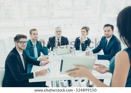 Businessmen and women  in conference room on presentation of new product