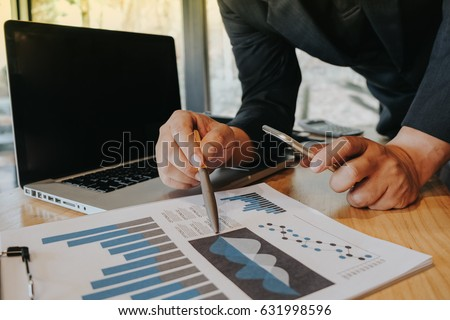 Businessmen are checking financial jobs, holding pen for right hand The left hand holds a smartphone. And find information from the notebook on a wooden desk.