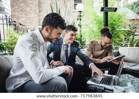 Businessmen are working together on wireless technology in a business meeting taking place in a bar courtyard.  Сток-фото ©