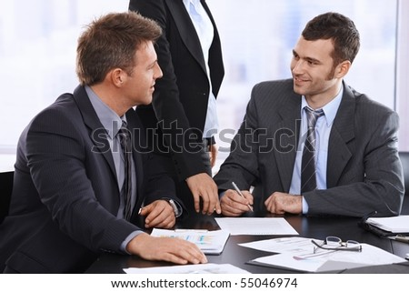 Businessmen discussing contract before sIgning, assistant waiting for document in office.