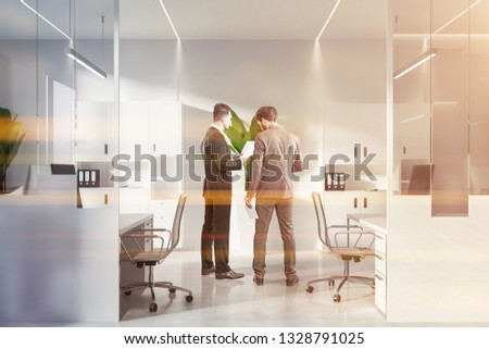 Businessmen discussing documents in interior of open space office with white and glass walls, white floor and white computer tables with bookcases near them. Toned image #1328791025