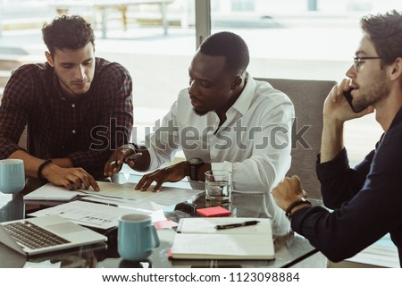 Businessmen discussing work sitting at conference table in office. Two men discussing work while another man is talking on mobile phone.