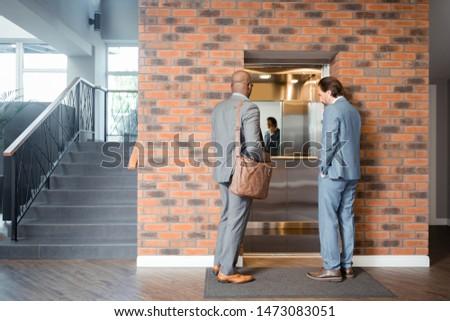 Businessmen entering lift. Two prosperous successful businessmen entering lift in the business center #1473083051