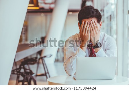 Businessmen feel stressed and tired sitting at his office with a laptop,mobbing concept Stockfoto ©