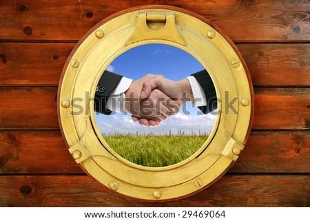 Businessmen green outdoor handshake view from boat round window [Photo Illustration]