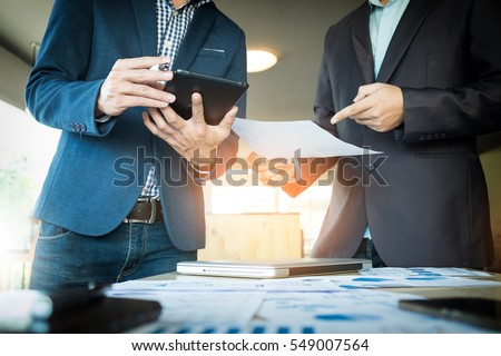 Businessmen hands pointing at document in touch-pad during explanation of new plan project data at meeting.