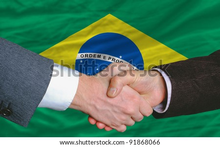businessmen handshake after good deal in front of brazil flag