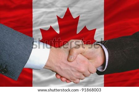 businessmen handshake after good deal in front of canada flag