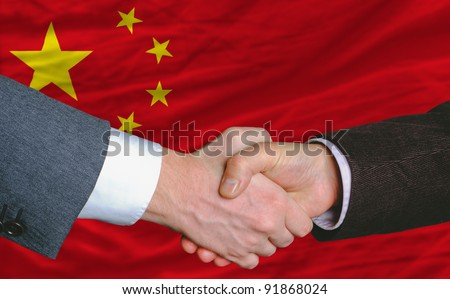 businessmen handshake after good deal in front of china flag