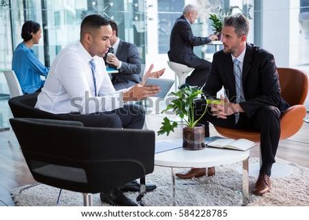 Businessmen having discussion over digital tablet in office