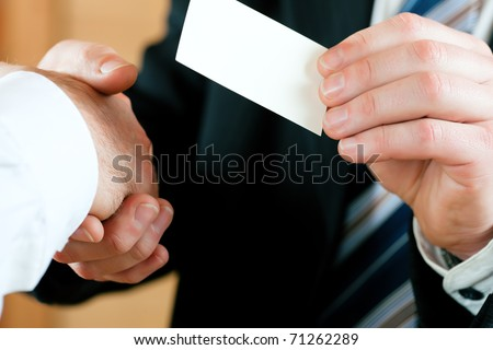 Businessmen having handshake, one handing business card over; only hands to be seen - stock photo