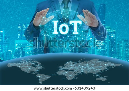 businessmen holding internet of things(IOTs) technology concept over night modern city building background