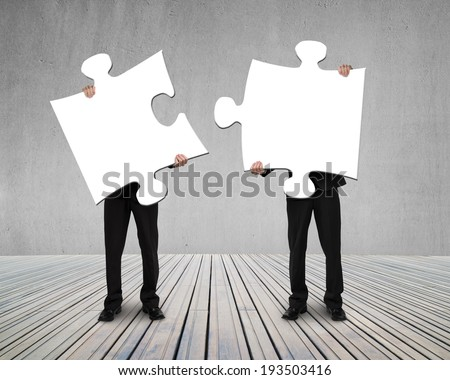 Businessmen holding two puzzles to connect on wooden floor Stock photo ©