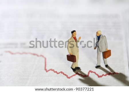 Businessmen in Conversation, two miniature models of businessmen in conversation standing over a red line graph .