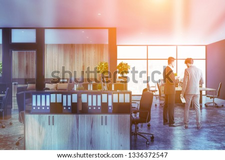 Businessmen in interior of open space office with black and wooden walls, concrete floor, panoramic window and rows of wooden computer tables with bookcases with folders near them. Toned image #1336372547