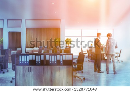 Businessmen in interior of open space office with white and wooden walls, concrete floor, panoramic window and rows of wooden computer tables with bookcases with folders near them. Toned image #1328791049