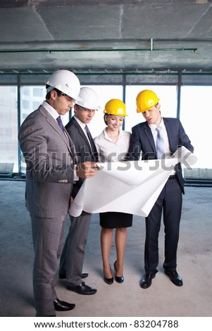 Businessmen look at a building site plan