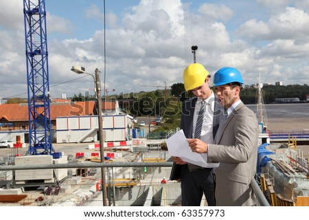 Businessmen looking at construction plan on site
