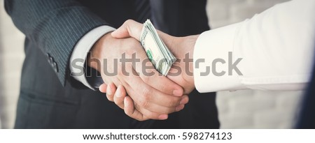 Businessmen making handshake with money in hands - bribery, corruption and venality concepts