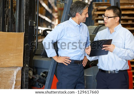 Businessmen Meeting By Fork Lift Truck In Warehouse